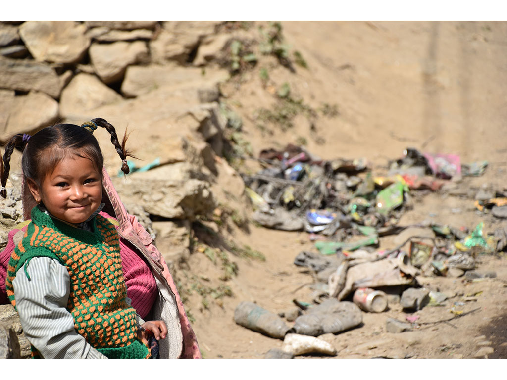 A gir happily looking into the camera of Mahila Avaz - Women's Voice. Behind her a pile of garbage. The women's project in Simikot initiates collective clean-ups in order to get rid of the mountains of trash in Simikot, Nepal.