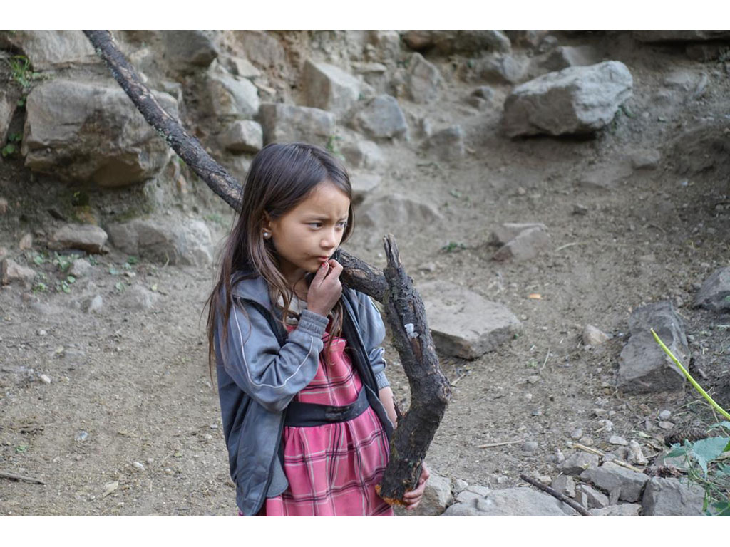 Thoughtful looking girl carrying wooden trunk. The women's project Mahila Avaz - Women's Voice fights to set an end to child labor and especially improve the living conditions of women and girls in Simikot.