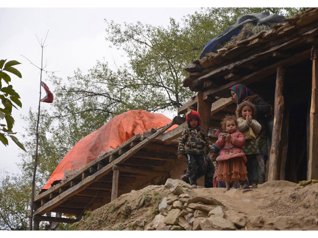 Children on a hill, cabins behind them, showing ''Namaste'' to a volunteer.