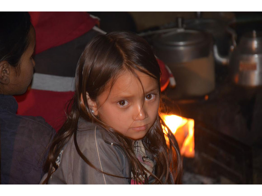 Sad looking girl in the kitchen of a house, behind her an oven with pots.