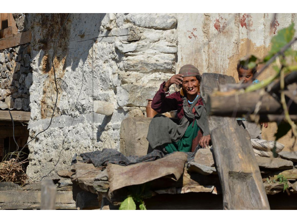 A woman sitting in the sun and smiling into the camera of the volunteer who is staying and helping in Simikot, Nepal.