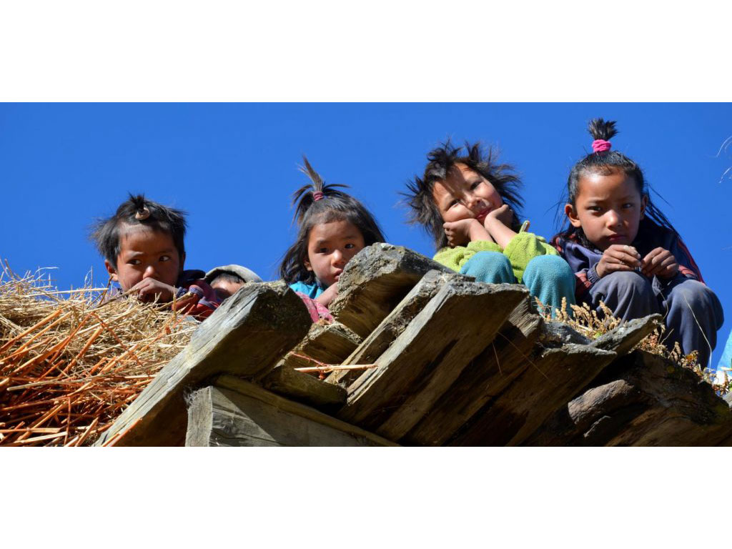 Four, partly making grimaces, nepalese kids looking down at volunteers.