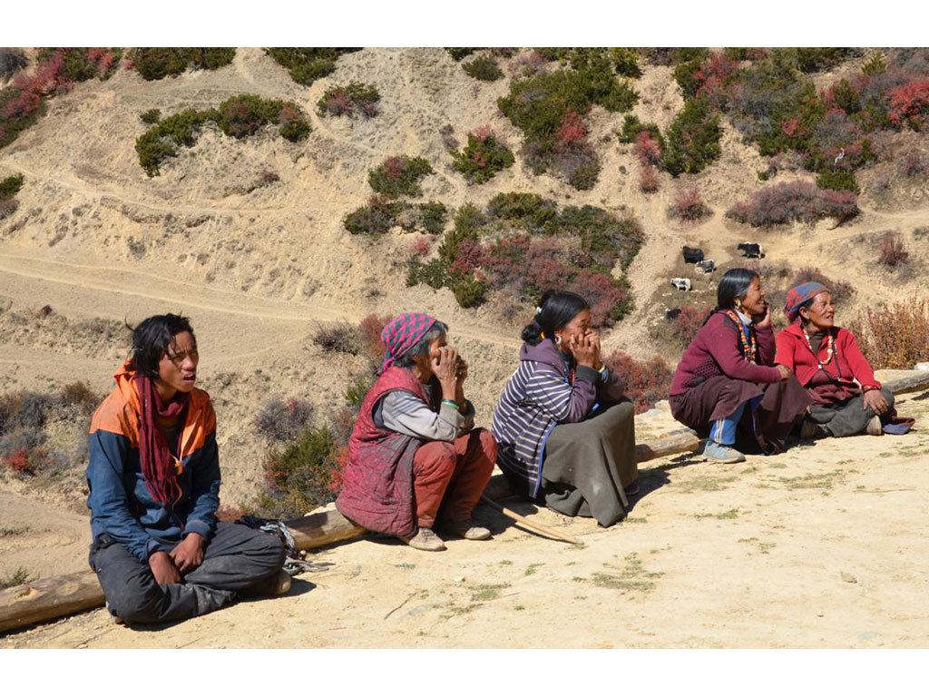 Women sitting on a roof, behind them barren landscape.