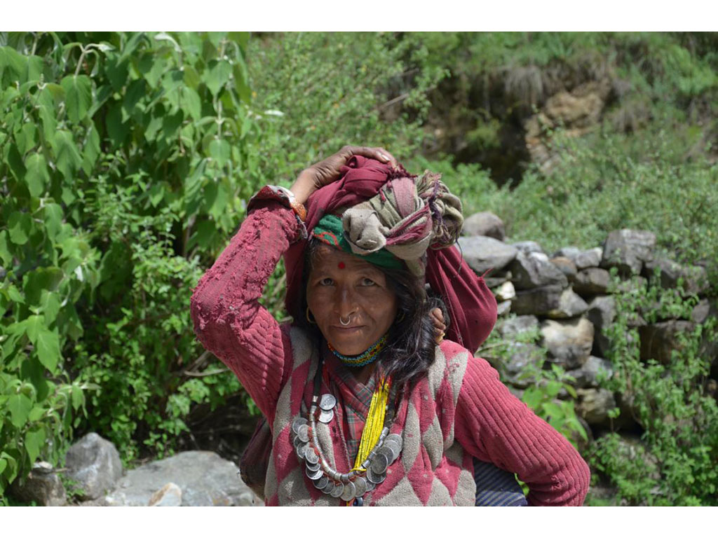 Woman with red cloth on her head and many necklaces and Bindi and child on her back looking into the camera of Nepal Trust Austria, the association that performs important develpoment co-operation and makes women empowerment possible.