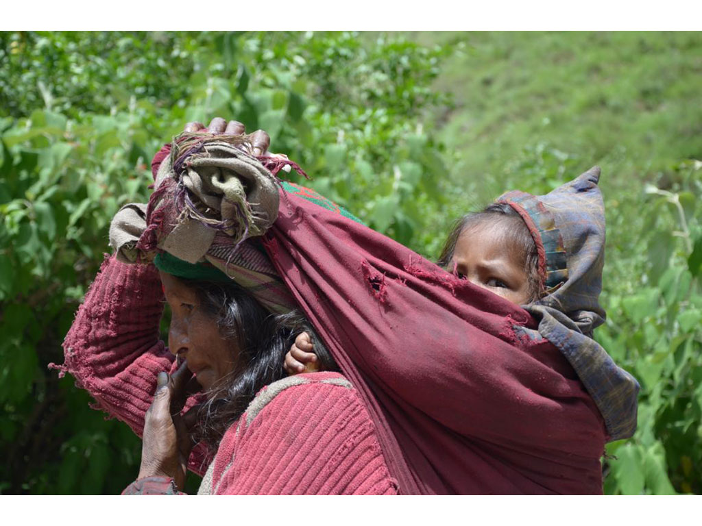 Woman with child on her back in Simikot, Nepal, where the association Nepal Trust Austria provides important development co-operation and advocates and makes women empowerment possible.