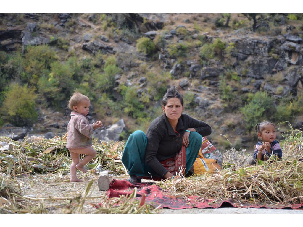 A mother with two children is being fotographed by a voluntary helper of Nepal Trust Austria.